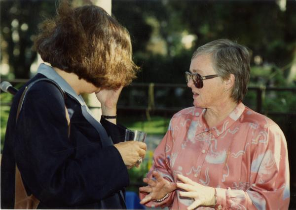 Library staff workers talk to each other at a staff retirement party, 1991