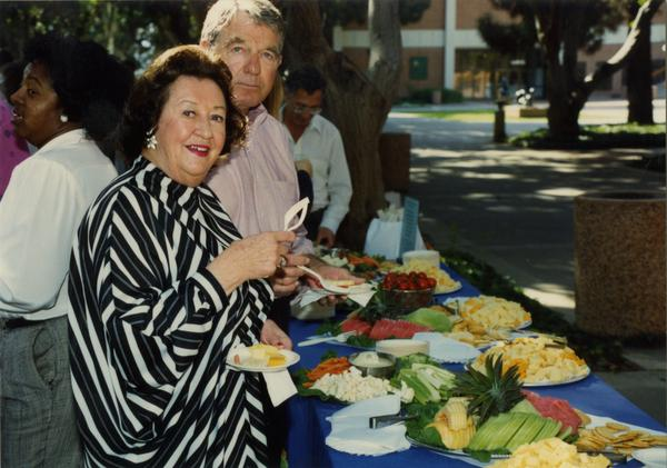 Library staff workers smile for the camera as they get their food at a staff retirement party, 1991