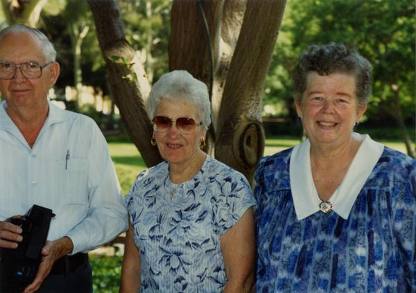 Three library staff members pose for a photo at a staff retirement party, 1991