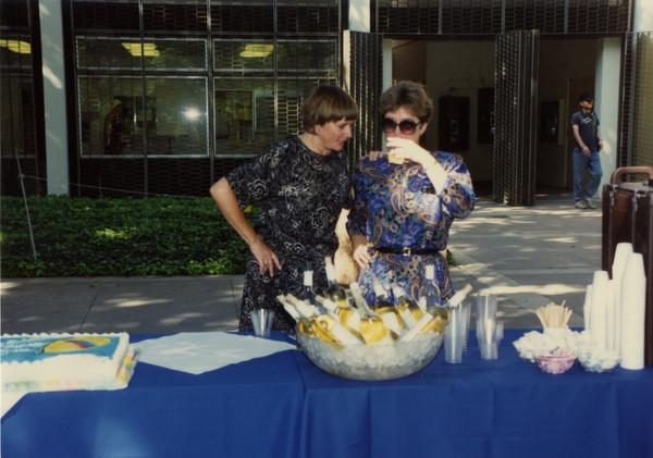 Library staff members gather around the wine table at the staff retirement party, 1991