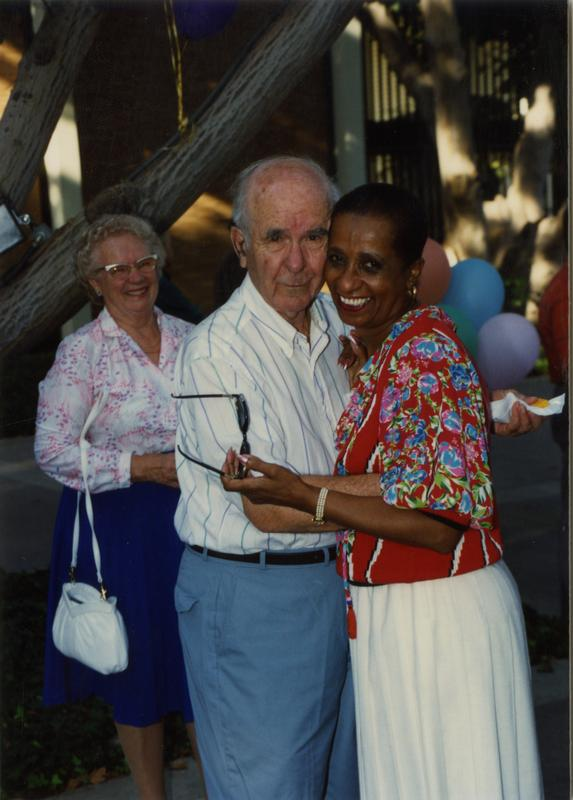 Library staff embrace each other for the camera with another staff member smiling in the background at a staff retirement party, 1991