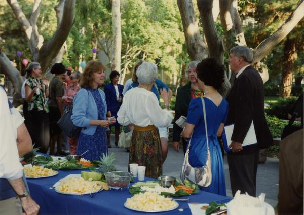Crowds at the library staff retirement party and food tables, 1991