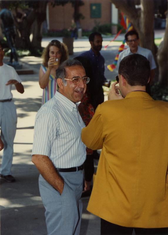 Candid photo of a library staff talking with another staff member at the staff retirement party, 1991