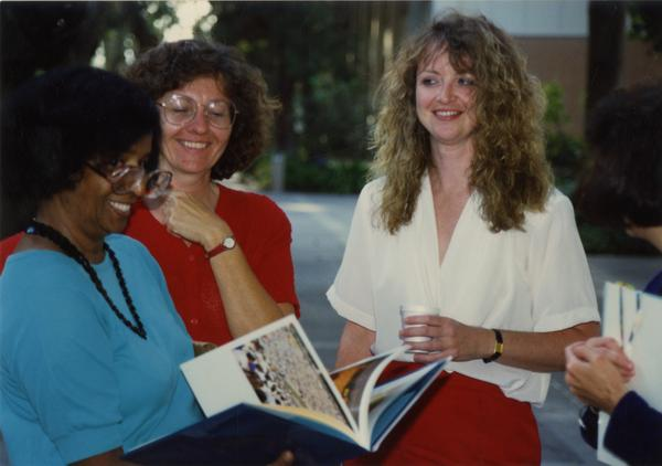 Library staff look on as another staff member looks through a book at the staff retirement party, 1991