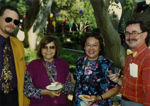 Library staff pose for a photograph, some holding food, at the staff retirement party