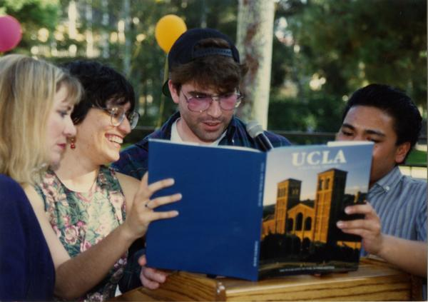 Library staff look through a UCLA book at the staff retirement party, 1991