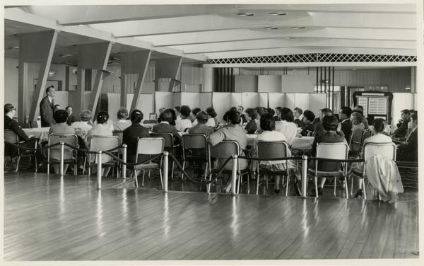 Crowd listens to former university librarian Lawrence Clark Powell speaking in Japan, ca. 1960