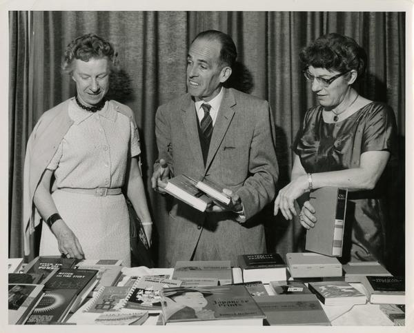 Lawrence Clark Powell and two unidentified UCLA library personell peruse through books laid out on a table during a visit to Japan, ca. 1960