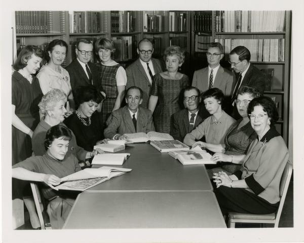 Group photo of the School of Library Service sitting around a table with a bookcase in the background