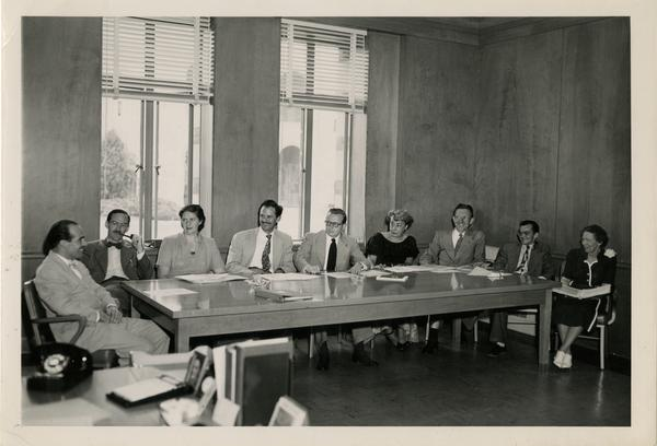 Library Science faculty sitting around the table looking at Lawrence Clark Powell