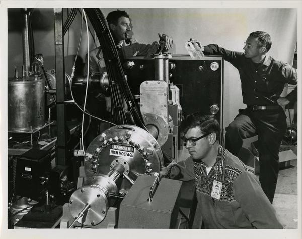 James L. Tuck, left, head of the Sherwood Project at Los Alamos, John Marshall, back right, John E. Osher, foreground, working on the new entropy-trapping equipment at the Los Alamos Scientific Lab, New Mexico