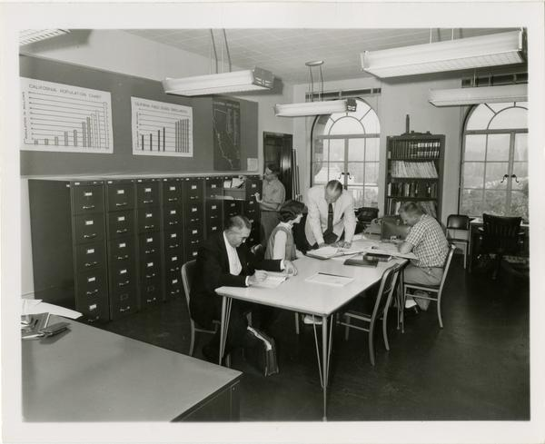 Unidentified group sitting in room in Moore Hall, looking over print materials