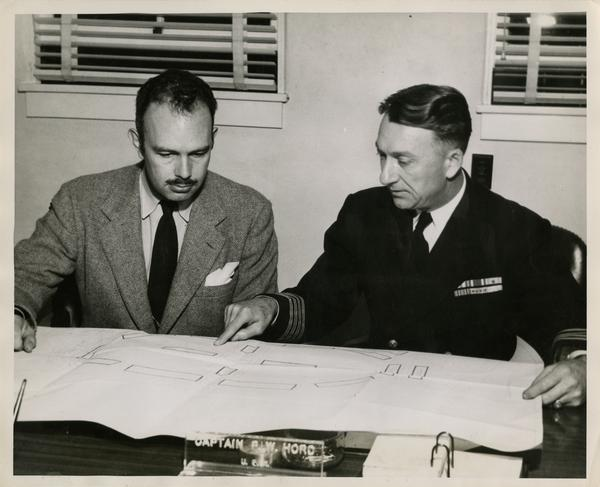 Dr. Franz N.D. Kurie discussing plans with Captain P.W. Hord in Navy Electronics Laboratory