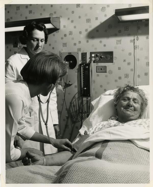 Nurse checks heart rate of patient
