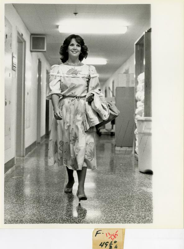 Nurse out of uniform walking down hall of facility