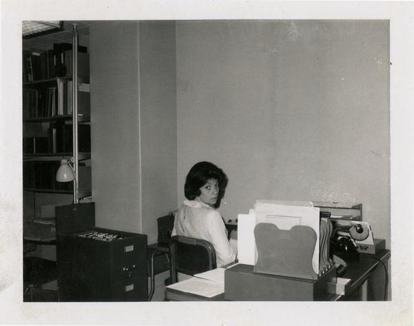 Cheryl Wolf, staff member of Oral History Program, sitting at desk