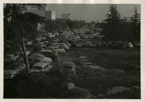Cars parked on a dirt lot with Barker Bros sign in background