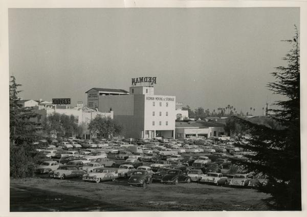 Cars parked on a dirt lot with Redman Moving & Storage sign in background