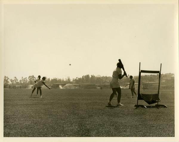Ball being pitched to woman at bat