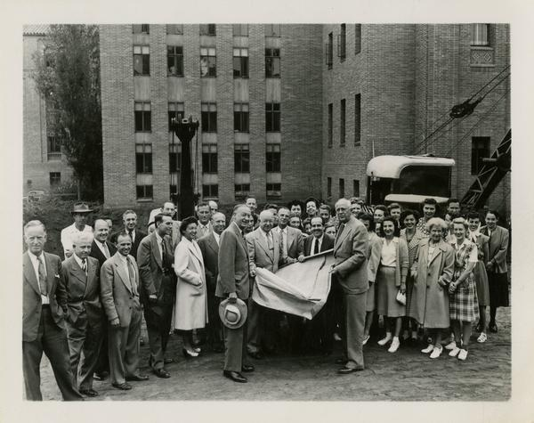 Dykstra, Dickson, Powell, and Keene among crowd gathering outside of Powell Library east wing, June 22, 1947