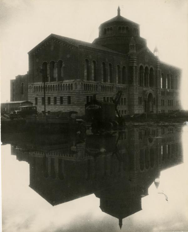 Powell Library and a reflecting pool formed from Winter rains, ca. December 1928