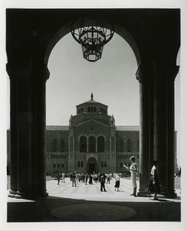 View of Powell Library through Royce Hall arches as students walk in quad