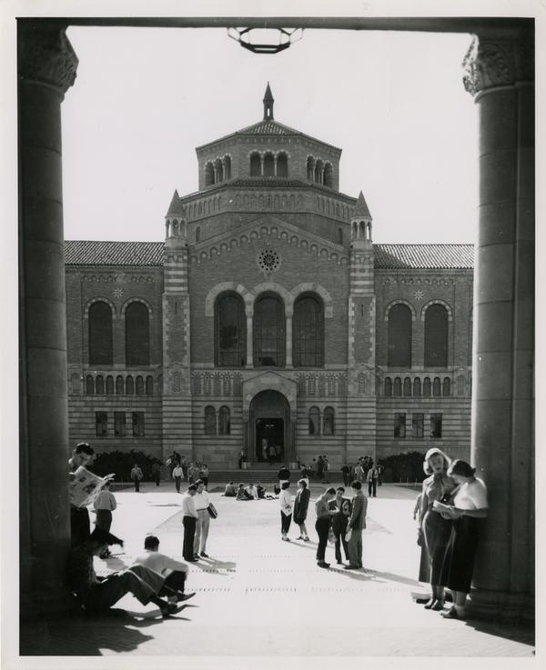 View of Powell Library through Royce Hall arches as students sit and talk in quad, ca. 1955
