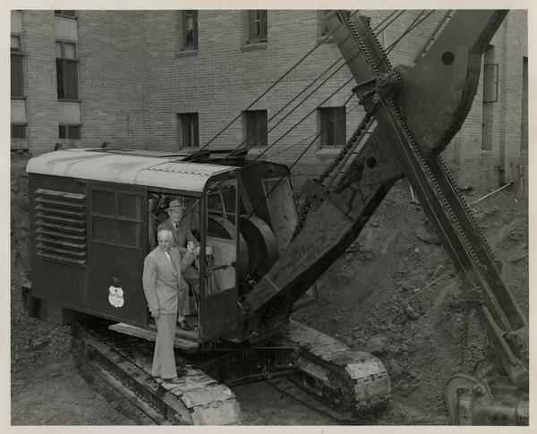 Two men posing by excavator scoop in construction area beside Powell Library, June 24, 1947