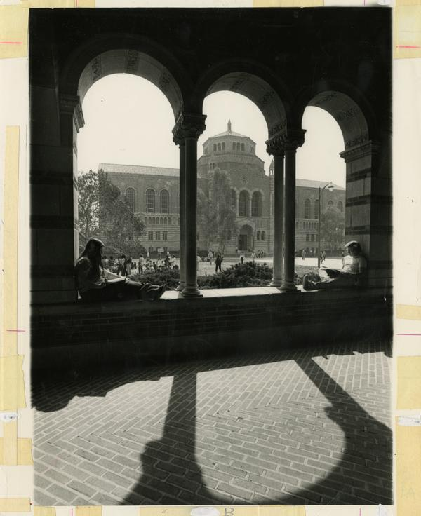 Students sitting in Royce Hall arches with Powell Library in background