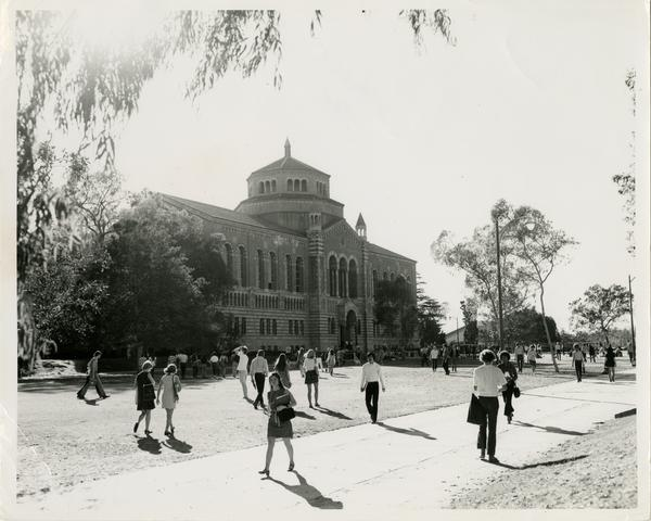 View of Powell Library as students walk by and through grass
