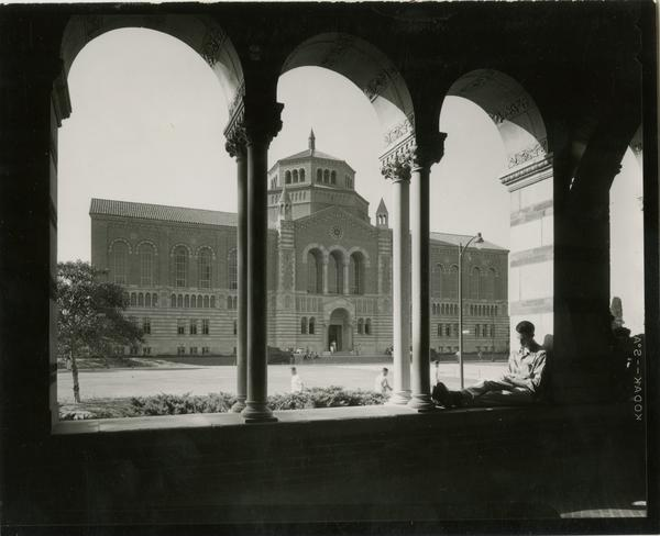 Student sitting in Royce Hall arches with Powell Library in background