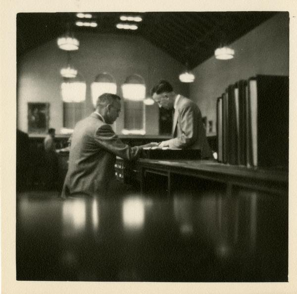 Richard O'Brien at the Reference Desk helping patron, 1949