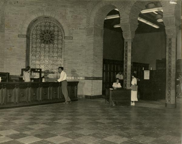 Library staff at Loan and Information desks assisting patrons at Powell Library, 1949