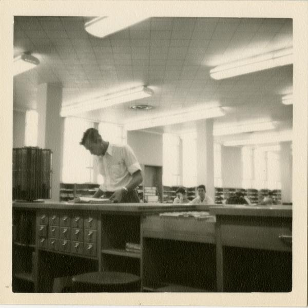 Jim Mink at reference desk in the Periodicals Room at Powell Library, 1949