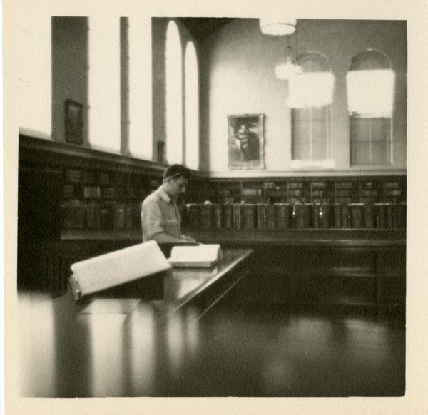 Looking towards the northeast corner of the Main Reading Room at Powell Library with a man standing at reference desk, 1949