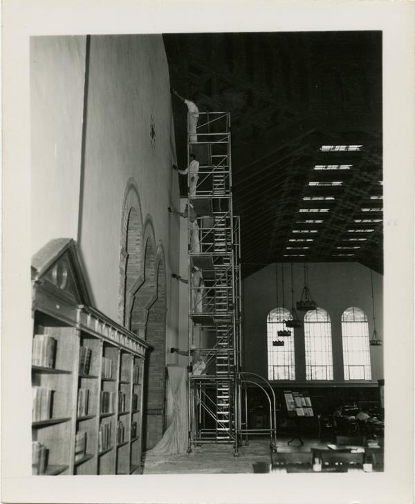 Workers painting the interior of Powell Library
