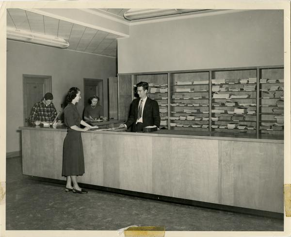 Library staff assisting a patron at the Periodicals reference desk