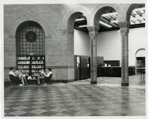 Students sitting in front of small library stack