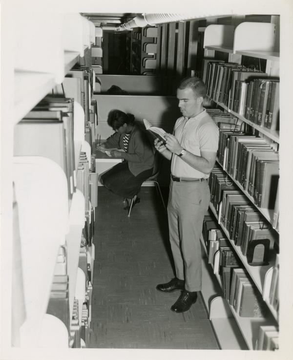 Student checking out a book in the Powell Library stacks