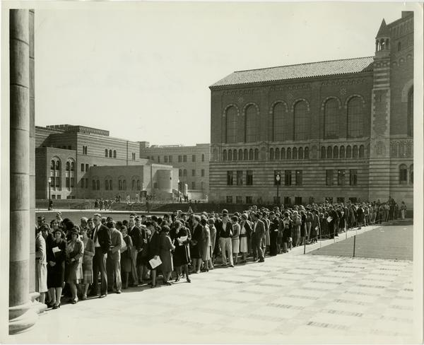 Powell Library in background as students stand in line to register for classes, February 1930
