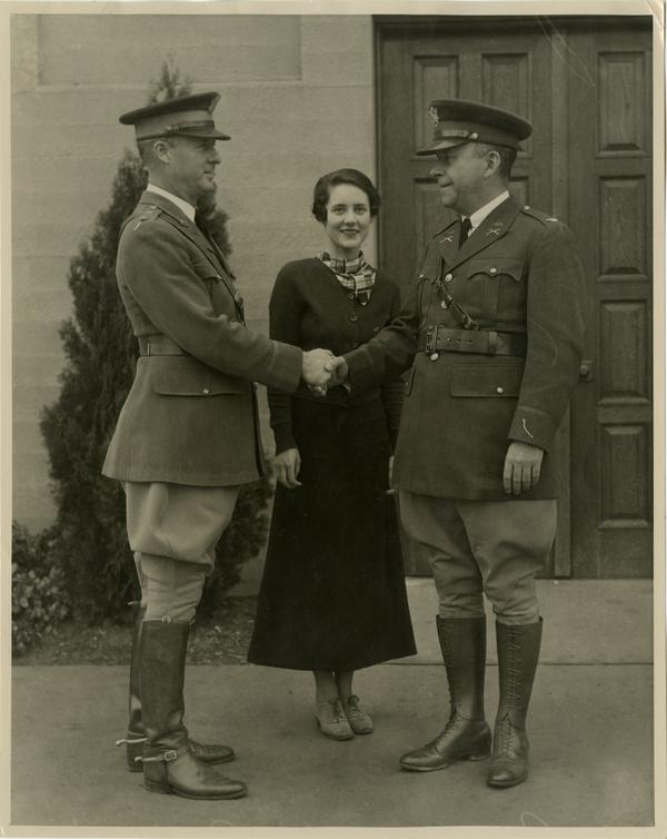 Photo of two men in uniform shaking hands while woman stands in center smiling