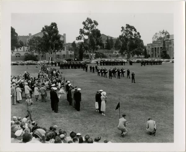 Crowd of civilians watch naval officer parade