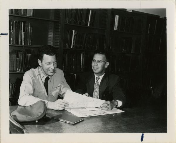 Officer and civilian look at materials, shelves of books in background
