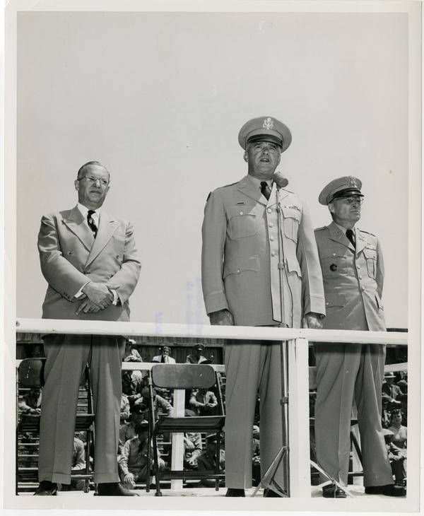 General William F. Dean addresses UCLA ROTC Cadet Regiment at Graduation parade while Chancellor Raymond Allen and Colonel Maxwell Thompson stand on either side, June 2, 1955