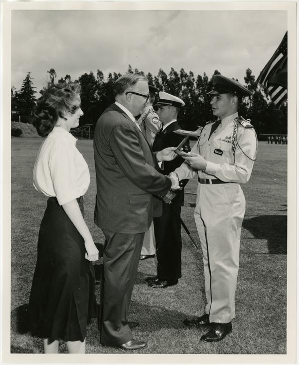 Chancellor Raymond B. Allen presents the Lockhead Aircraft 104-B Starfighter model to Cadet Lieutenant Colonel Bernard Katzman, Air Force ROTC at the annual review of the UCLA ROTC, May 2, 1957