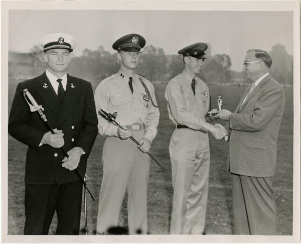 Chancellor Raymond B. Allen congratulating cadets, ca. 1956