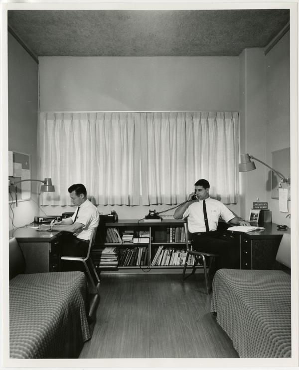 Interior view of dorm room with students at desks, ca. 1960