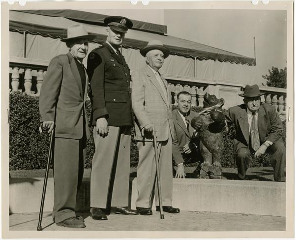 Photo of Roger J. Adams, General William F. Dean, William A. Baker, Harry W. Henry, and Joseph O. Morris Pasadena with Bruin mascot at Pasadena Civic Auditorium following the Kick-Off Luncheon, December 31, 1953