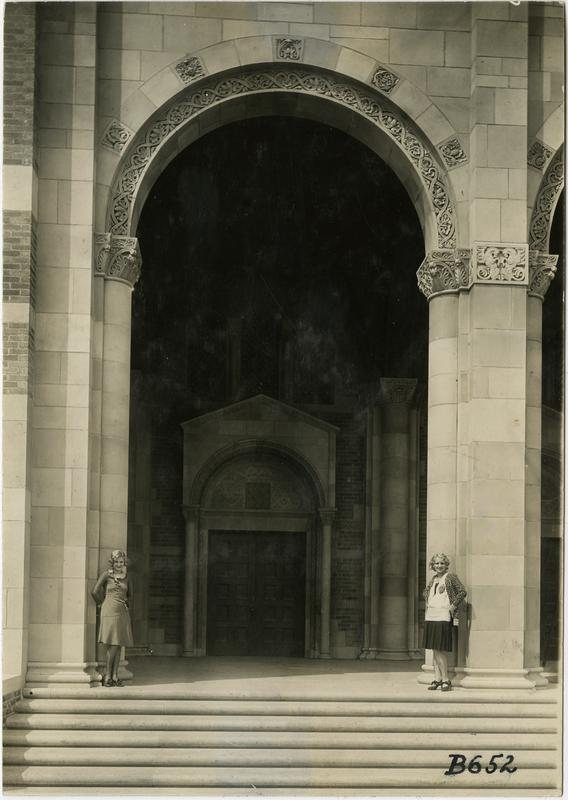 Two women standing underneath arcade of Royce Hall