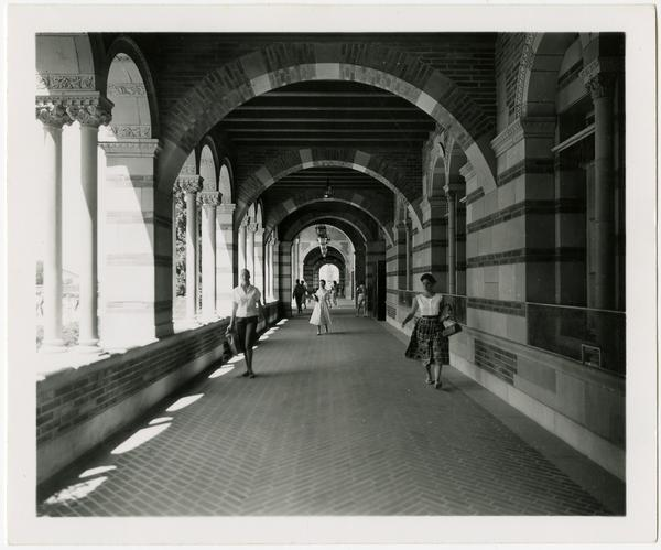 View of students walking down arcade of Royce Hall, ca. July 1958